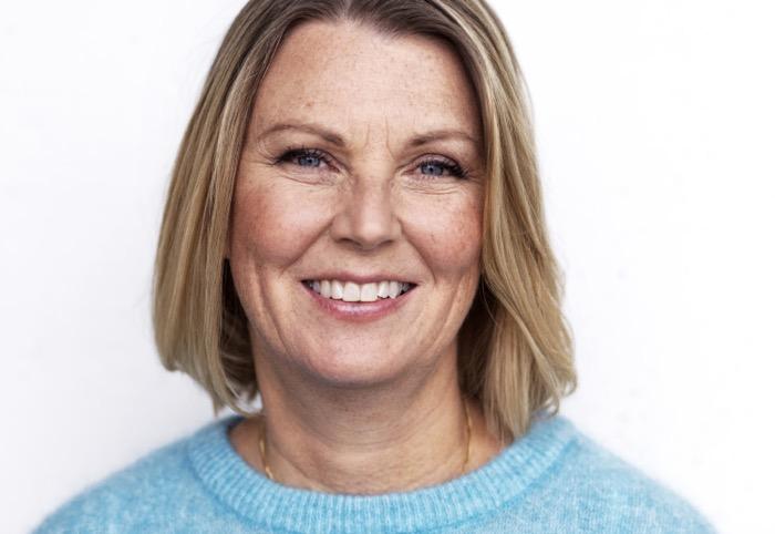 Porträtt på Petra Krantz Lindgren i ljust blå tröja, bakgrunden är vit.