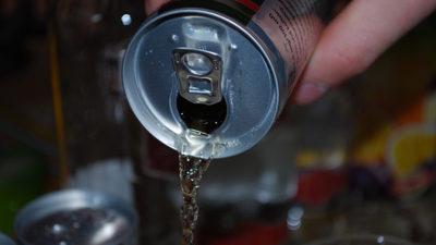 Foto på någon som häller upp energidryck i ett glas.