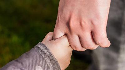Foto på en vuxen och ett barn som håller varandra i händerna.