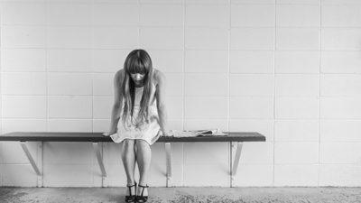 Foto på en tjej som ser ledsen ut och som sitter på en bänk.