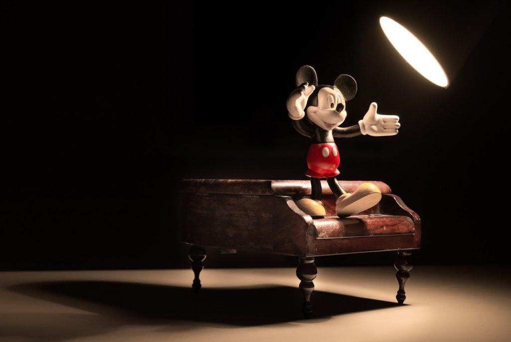 Bild på karaktären Musse Pigg som sitter på ett piano och slår ut med armarna.