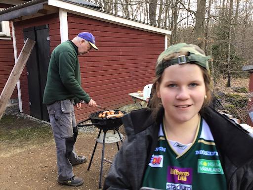 Peter grillar mat i bakgrunden. Iza står i förgrunden och tittar in i kameran.