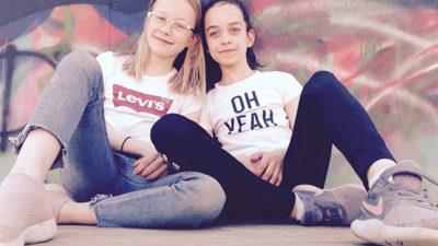 Foto på två tjejer som sitter lutade mot en vägg.