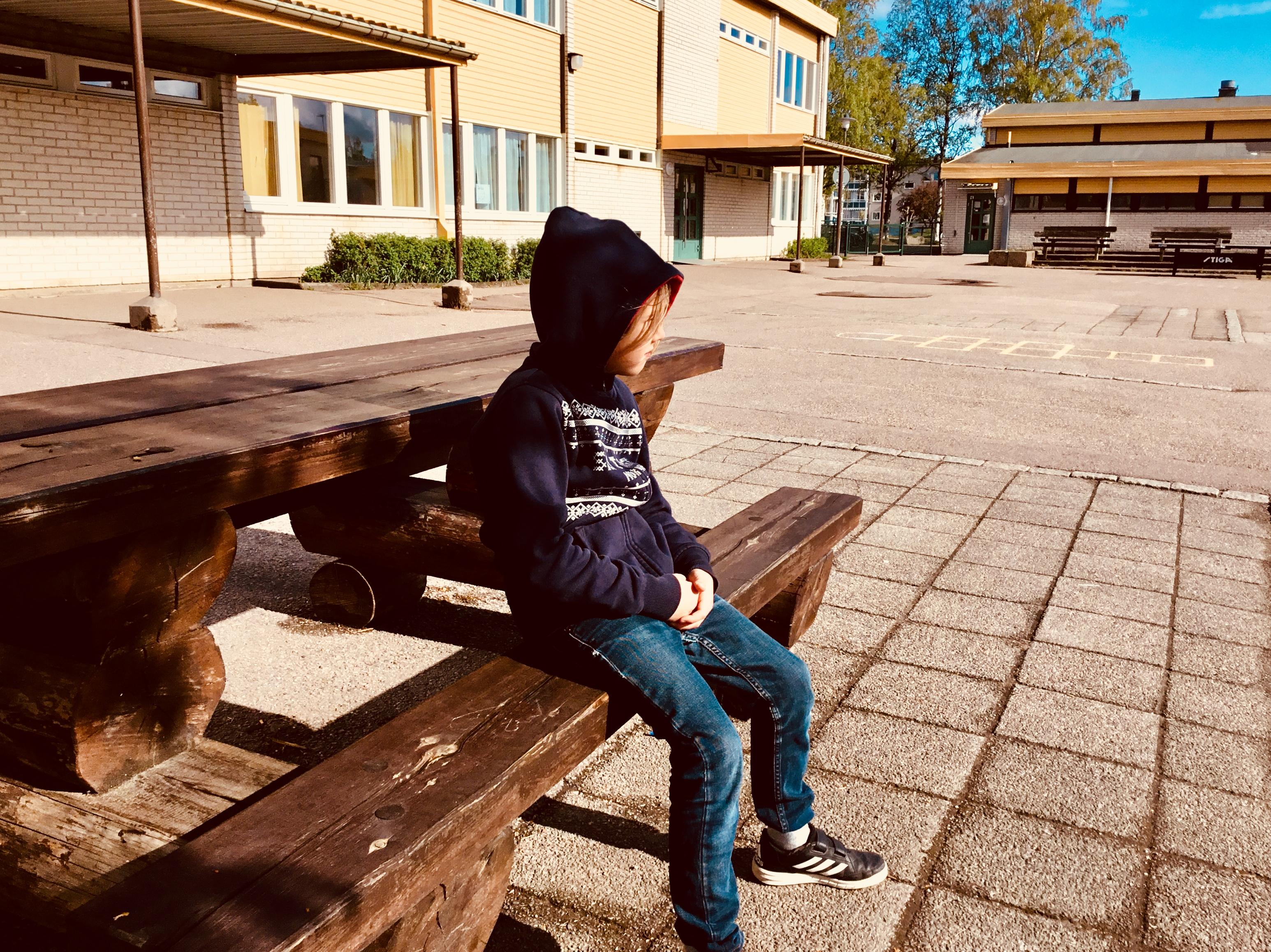 Ett barn sitter på en bänk i solen på en skolgård.