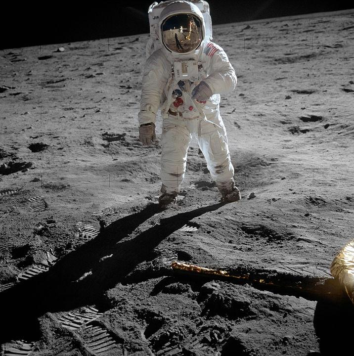 En person i stor rymddräkt står på månens uta. Bakifrån lyser solen starkt, men himlen är helt mörk. Man kan inte se ansiktet på personen eftersom den har en stor rymdhjälm på sig.