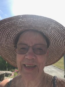 Eva står i motljus. Hon har på sig en stor solhatt och halvmörka glasögon. Hon är ganska rynkig. Hon ser glad ut.