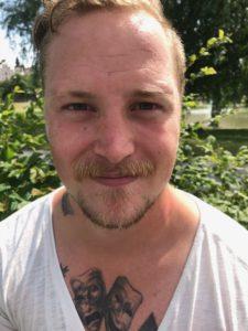 Kalle har tatueringar på bröstet som syns ovanför tröjans kant. Han har skägg, mustach och kort hår som vågar sig i pannan. Han ser lite lurig, men glad, ut.