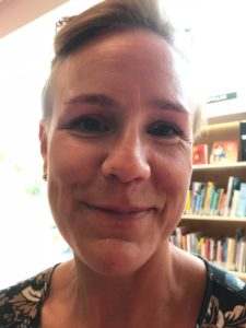 Kristina står inne på biblioteket. Hon har kort hår och ler mot kameran så hon får smilgropar.