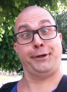 Kristofer har glasögon och är rakad på huvudet. Han gör en rolig med korsade ögon för att se roliga ut.