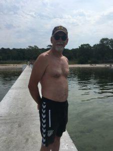 Stefan står på en badbrygga i badbyxor. Han har solglaögon och keps på sig.