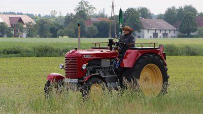 En bonde åker en röd traktor.
