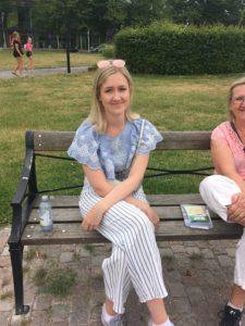 Viktoria sitter på en bänk där det är en stor gräsmatta i bakgrunden. Hon har en blus med volang på och luftiga långbyxor. Hon har axellångt hår och solglasögon uppskjutna på huvudet.