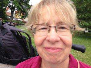 Anna står nära kameran. Hon har glasögon, ser glad ut och ar fjunig lugg.