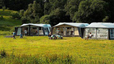 Några husbilar står i kanten på ett skogsbryn. De har sina förtält uppsatta och utanför sitter människor på tältstolar.