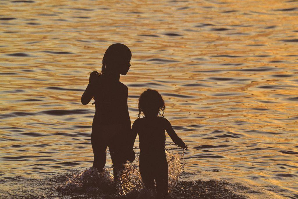 Två barn står med vatten upp till knäna i vattenbrynet. Det är kväll så det går inte att urskilja detaljer utan bara barnens siluetter.