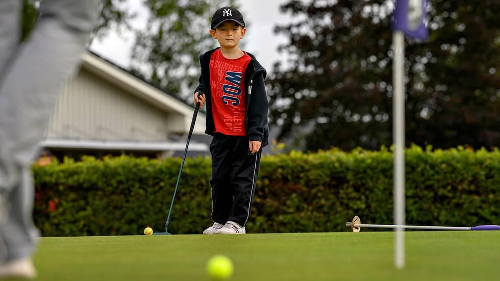 Erik står på golfbanan. Han har keps och träningsbyxor på sig. Han har klubben i handen. Han tittar bort mot bollen som han har puttat.
