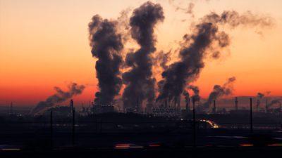 I solnedgången står det flera stora fabriker som släpper ut stora moln på himlen.