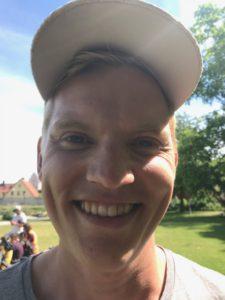 Linus har keps som gör att hans ansikte faller i skugga. Han ler stort och får massa skrattrynkor runt ögonen. Han har kort hår som inte syns under kepsen.