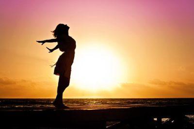 En kvinna sträcker händerna bakåt. bakom henne är solen på nedgång