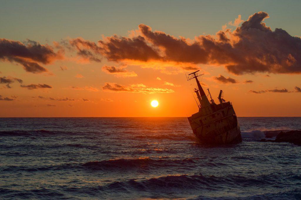Bild på en båt som seglar i solnedgången. På havet syns vågor och det är några enstaka moln på himlen.
