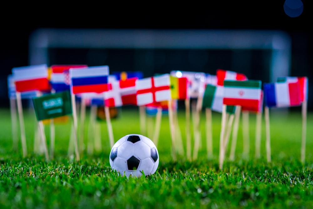 Massa små flaggor på pinnar är nedstuckna i gräset på en fotbollsplan. Framför dem ligger en liten fotboll.