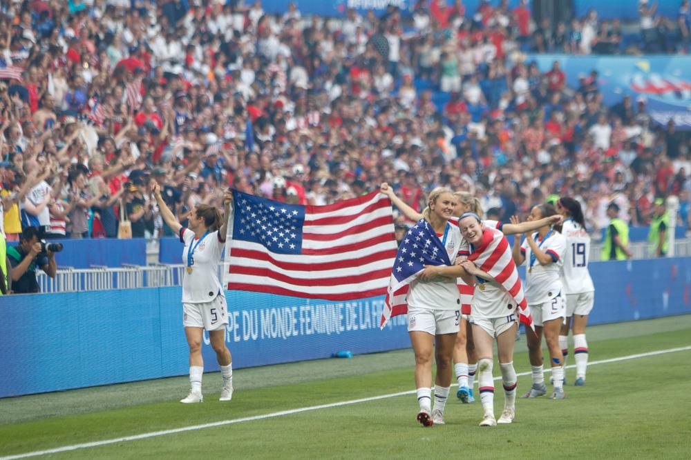 USA:s lag springer längs med kanten av planen. De håller upp en stor amerikansk flagga, vinkar åt publiken och kramar varandra.