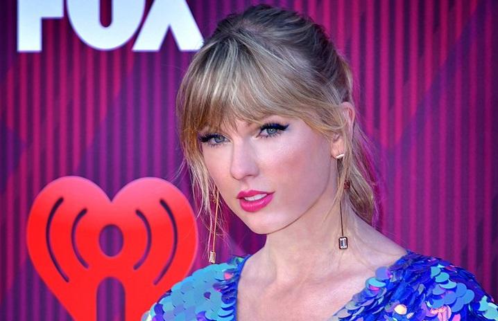 Taylor Swift på en gala. Hon har mycket smink, hår i tops och en klänning gjord av stora paljetter.