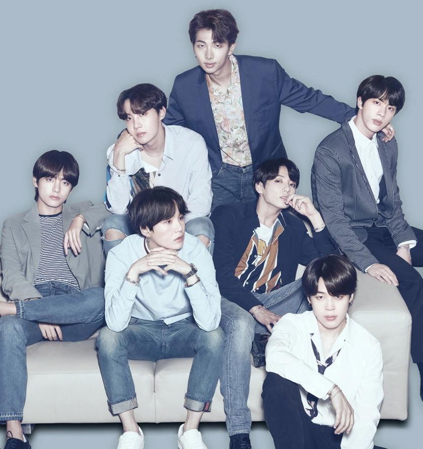 Bandet sitter och står runt en soffa. De flesta av dem har lång lungg som hänger ner i pannan. De flesta har också jeans och en cool t-shirt. Några har en modern kavaj. De står i olika positioner och ser coola ut.