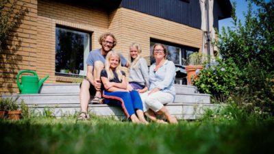 Skånsk familj sitter framför sitt hus