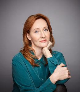 Rowling håller huvudet i handen. Hon ser ut att vara ungefär 45 år gammal. Hon tittar ganska fundersamt och allvarligt in i kameran.