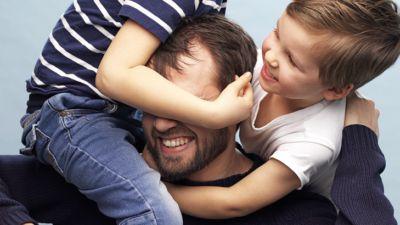Två barn klättrar på Mattias. Den ena håller om Mattias huvud. Alla skrattar och ser busiga ut.
