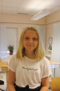 Selma står i ett klassrum. Hon har långt hår ner till axlarna och ler litegrann.