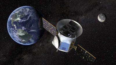 """Tess ute i rymden mellan jorden och månen. Det är en stor rund metallburk med """"vingar"""" som är solpaneler."""