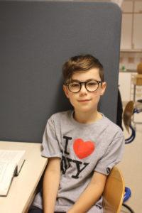 Vincent sitter mot en vägg i ett klassrum. Han ser ut att vara påväg att säga något. Han har kort hår och glasögon med kraftiga bågar.