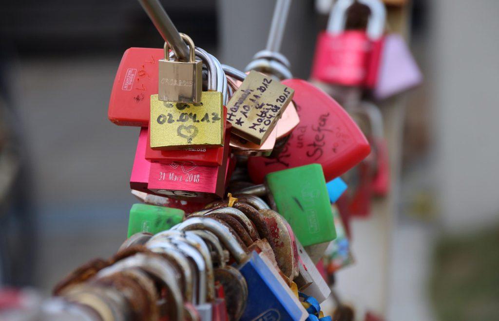 Lås som sitter på en bro med text och hjärtan på dem