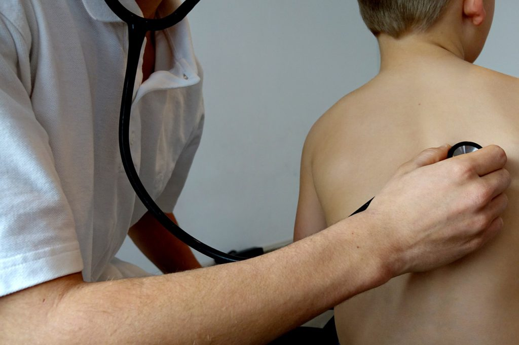 En läkare undersöker ett barn med sitt stetoskop