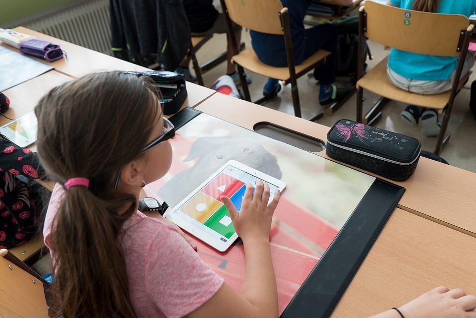Ett barn sitter med en läsplatta vid en skolbänk
