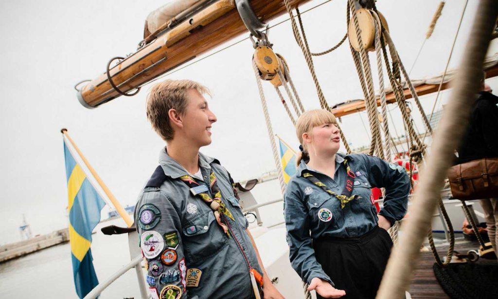Malcolm och Erik står på däcket på fartyget. Runt dem hänger stora trossar och man ser masten i bakgrunden. De har båda på sig scoutskjortor med massa märken på.