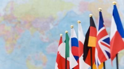 G7-ländernas falggor hänger i rad. Bakom dem syns en världskarta.