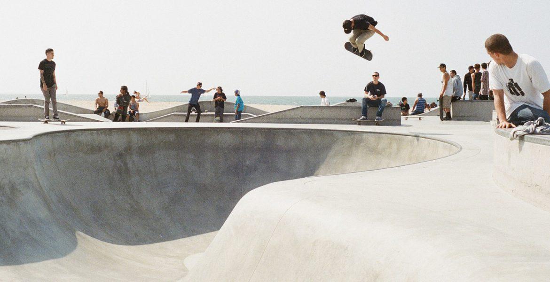En skateboardpark vid havet. En person åker i en bowl och hoppar högt upp i luften med brädan. Runt om står människor och tittar på.