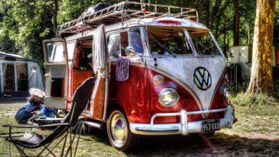 En volkswagenbuss står i ett skogsbryn. Dörren är öppen på sidan och där inne syns möbler. Utanför står några stolar och det hänger kläder på dörrarna.