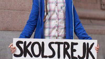 Greta Thunberg står i en rutig skjorta, en blå tjocktröja och håller i en skylt där det står Skolstrejk för klimatet