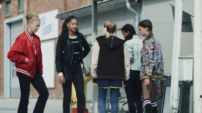Adja Krook i tv-serien Dröm står och pratar med några personer.