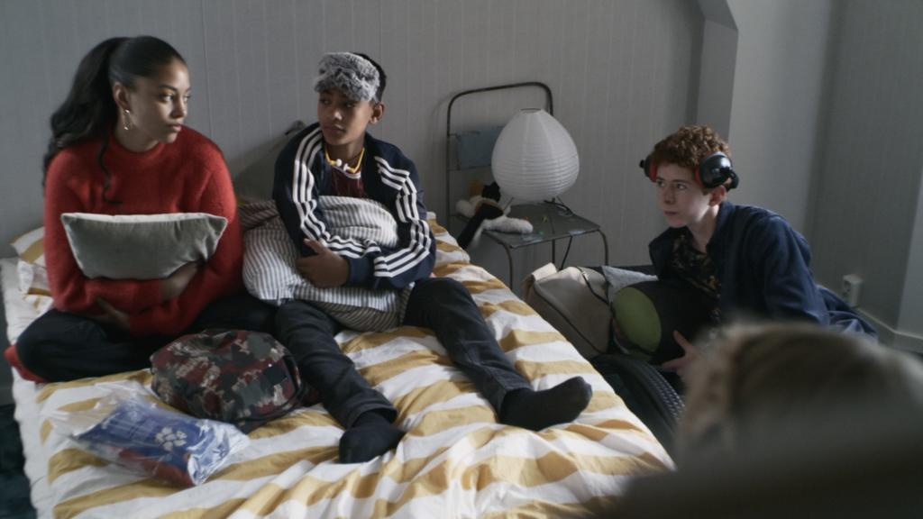 Adja Krook sitter på en säng med två kompisar.