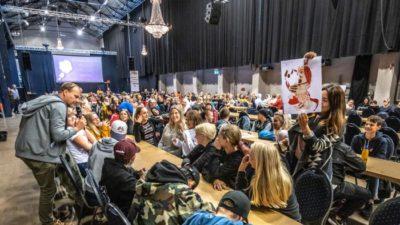 Människor sitter runt massa bord och väntar på workshop