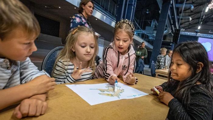 Fyra barn har samlats runt en teckning