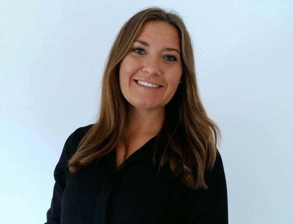 Porträttbild av Selina Karlsson i svart skjorta och utsläppt hår.