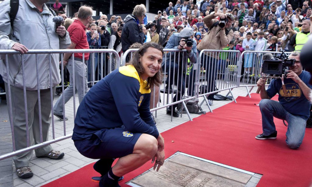 Zlatan står på huk och blir fotograferad
