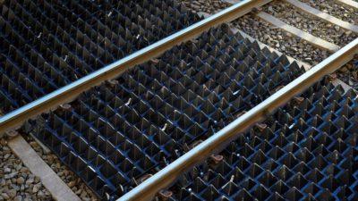 Spetsiga pyramidmattor över ett tågräls