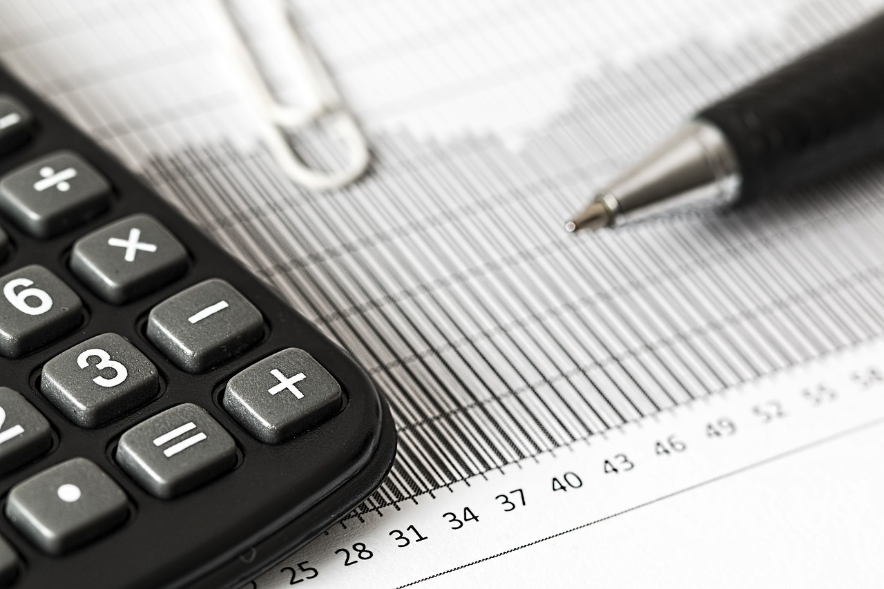 En miniräknare, papper, ett gem och en penna